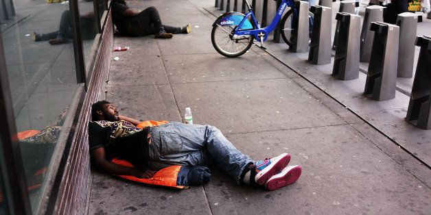 NEW YORK, NY - AUGUST 21:  A man sleeps on the ground outside the Port Authority Bus Terminal on August 21, 2014 in New York