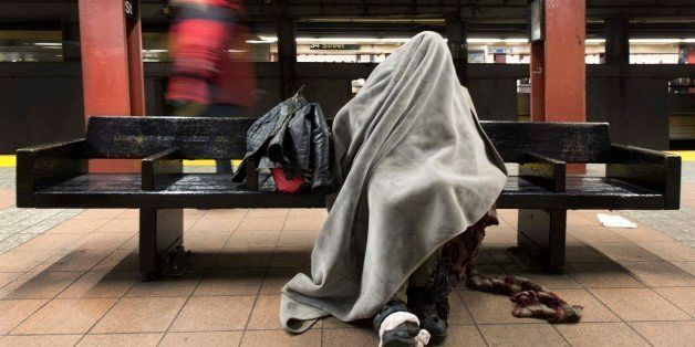 A homeless man rests under a blanket while sitting on a bench in a New York subway station, Tuesday, Jan. 28, 2014. Monday ni