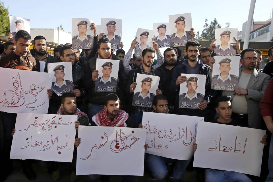 Supporters of Jordanian pilot, Lt. Muath al-Kaseasbeh, who is held by Islamic State group militants, hold posters of him with