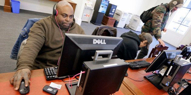In this Feb. 19, 2015 photo, Jeffery Bailey, left, works at a public computer at the Nashville Public Library in Nashville, T