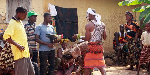 In this photo taken on Feb. 23, 2015, traditional healers, center, take part in a exorcism as villagers hand them a chicken,