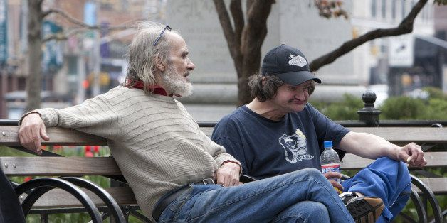 New York, NY.  A pair of homeless men sit and pass the time on a park bench in lower Manhattan.