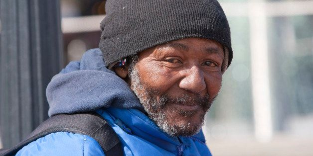 Happy homeless african american man outdoors during the day.