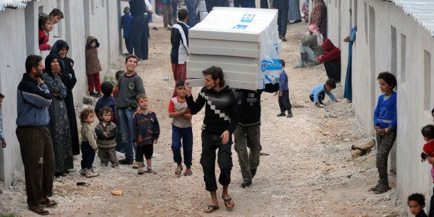 IDLIB, SYRIA - NOVEMBER 19: Members of Hayrat Humanitarian Aid Association distribute aids to Syrian families who were escape
