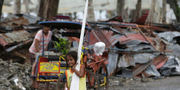 A typhoon survivor carries an oar and a life vest which were donated by the charitable organization Urban Poor Associates nea