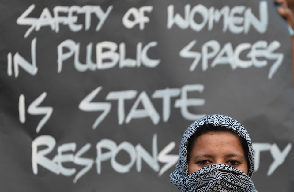 A woman holds a placard during a silent protest titled 'Women in Black for Peace' on the eve of International Women's Day in