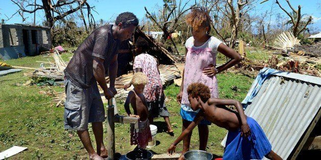 Locals pump water from the well in their coastal village amongst debris left in the aftermath of Cyclone Pam on the Vanuatu i