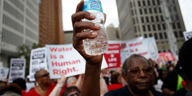 DETROIT, MI - JULY 18 : A man holds a bottle of water as he joins other demonstrators protesting against the Detroit Water an