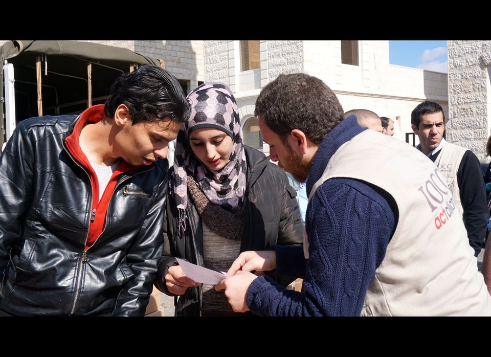 A staffer from International Orthodox Christian Charities (right) reviews the relief items that Duha (center) and her husband