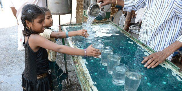 This photo taken on March 18, 2015 shows girls getting a glass of water at a free drinking water distribution stand in Hydera