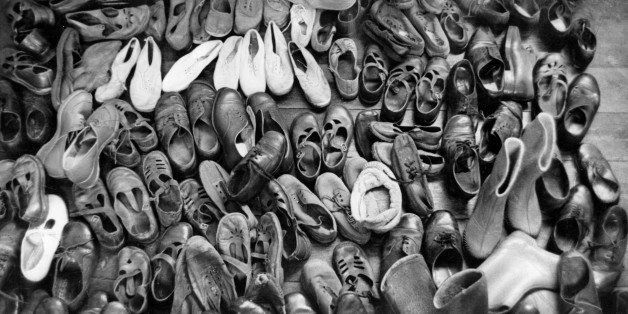 Dozens of pairs of children's shoes, piled up ready for cleaning.  Original Publication: Picture Post - 5690 - A New Way with