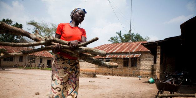 African woman carrying firewood in a backyard.