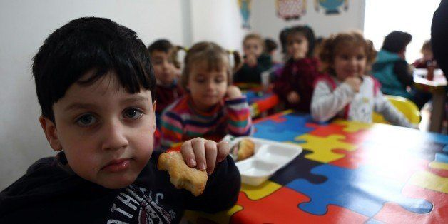 Children eat cakes in a Syrian private school in Mersin, southern Turkey on March 11, 2015 where at least 200.000 Syrians liv