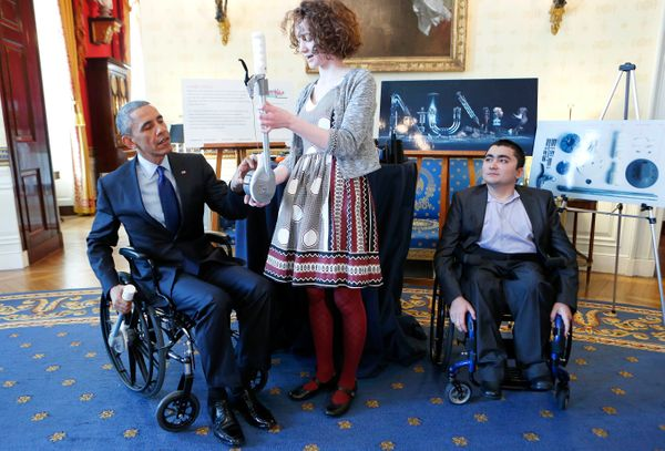 President Barack Obama tries an attachable lever, created by Kaitlin Reed, that can make wheelchair movements easier, while M