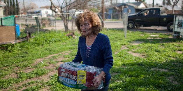 EAST PORTERVILLE, CA - FEBRUARY 11:  Evangeline Chavez receives drinking water from Donna Johnson who distributes drinking wa
