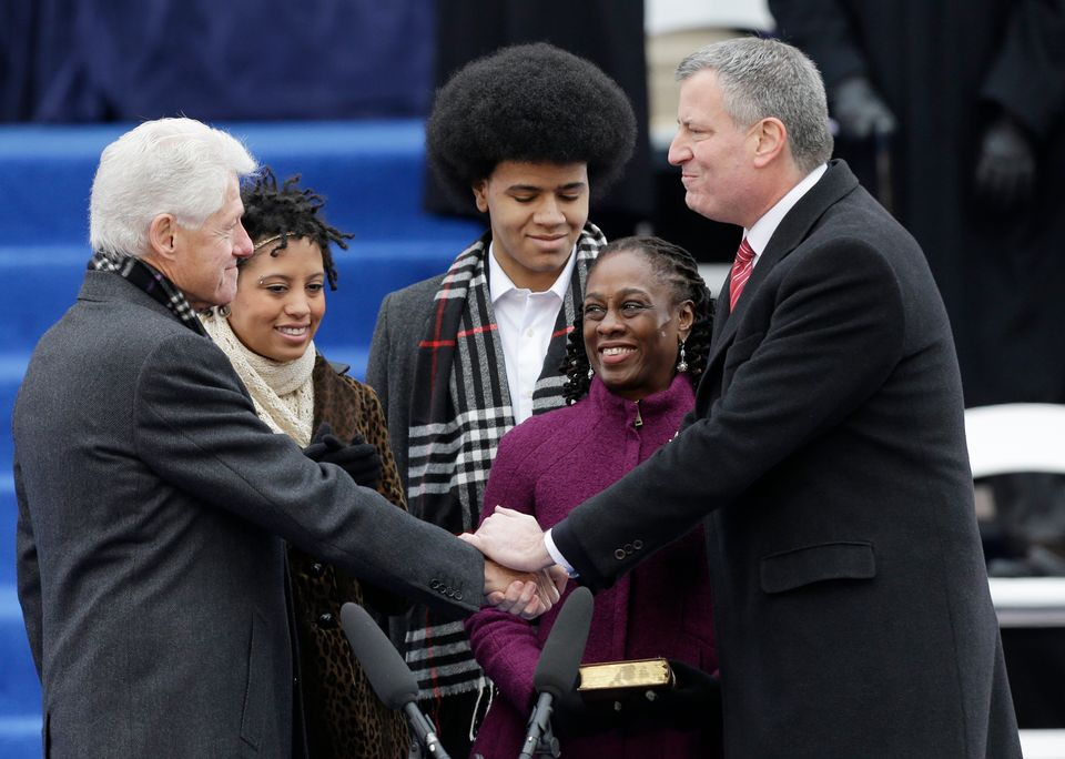 Former President Bill Clinton, administers the oath of office to Mayor-elect Bill de Blasio as his wife Chirlane McCray, seco