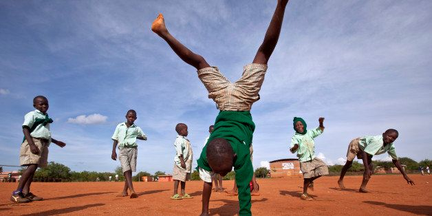 In this photo taken Wednesday, Nov. 21, 2012, a young schoolboy makes handstands as he plays with others during break in the