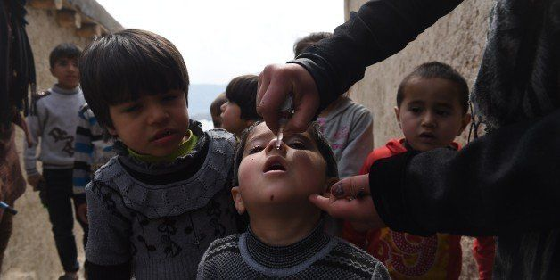 An Afghan health worker administers polio vaccine drops to a child on the second day of a vaccination campaign in Kabul on Ma