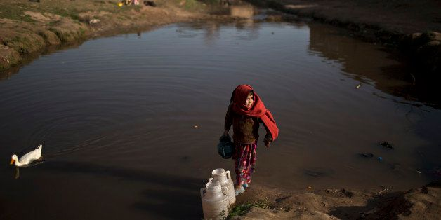 An Afghan refugee child collects water from a polluted stream to be used by her father to fix the walls of their mud home on