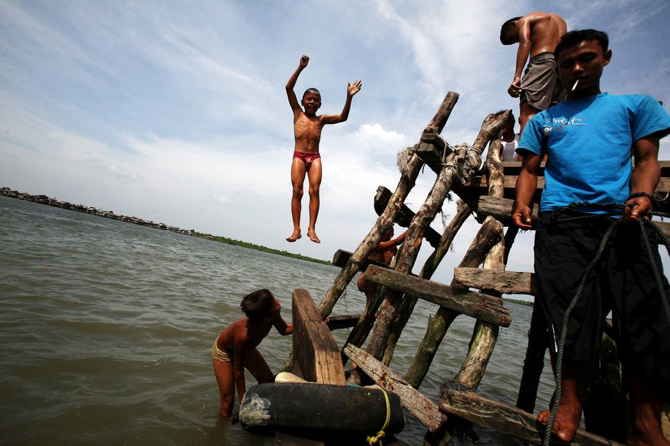 An Indonesian boy jumps into the sea while playing with his friends at a fishermen village in Belawan, North Sumatra, Indones