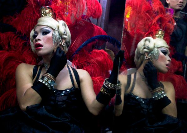 In this late Saturday, July 7, 2012 photo, an Indonesian transvestite applies make up as she prepares before performing in a