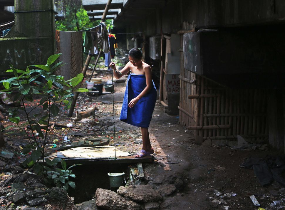 An Indonesian woman collects water for her shower from a well at a slum under a flyover in Jakarta, Indonesia, Thursday, Marc