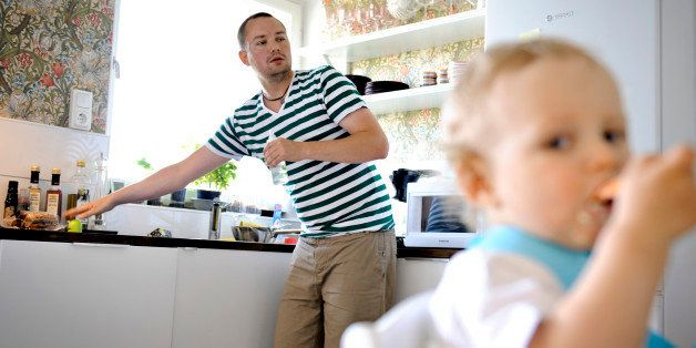 In this Wednesday, June 29, 2011 photo, Henrik Holgersson cares for his son, Arvid, in the kitchen of their home in Stockholm
