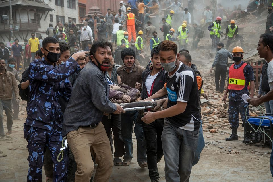 Emergency rescue workers carry a victim on a stretcher after Dharahara Tower collapsed on April 25, 2015, in Kathmandu, Nepal