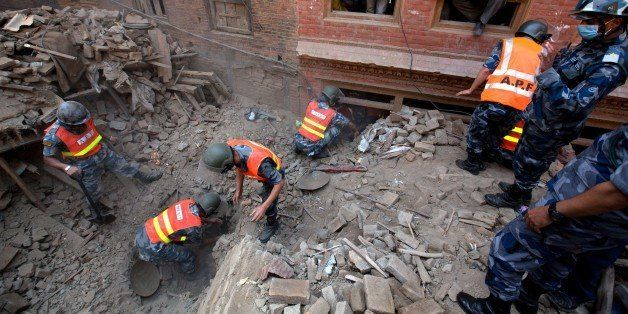Nepalese Military Police officials search through rubble in the earthquake damaged area of Bhaktapur on the outskirts of Kath