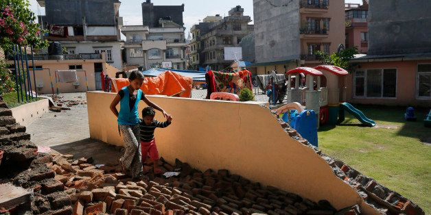 A young girl walks with a boy over a collapsed school playground in Kathmandu, Nepal, Monday, April 27, 2015. A strong magnit