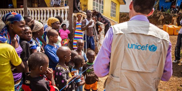 In this photo taken on Thursday, Feb. 26,  2015, A  UNICEF aid worker, right, visits a home that has been quarantined due to
