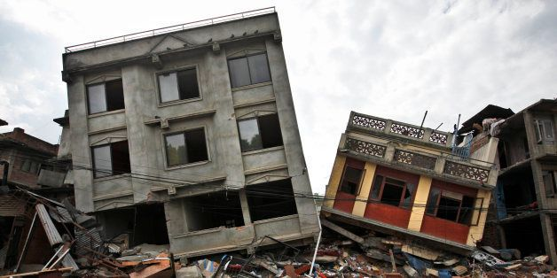 A Nepalese man walks past damaged buildings in Lalitpur, on the outskirts of Kathmandu, Nepal, Thursday, April 30, 2015. In m