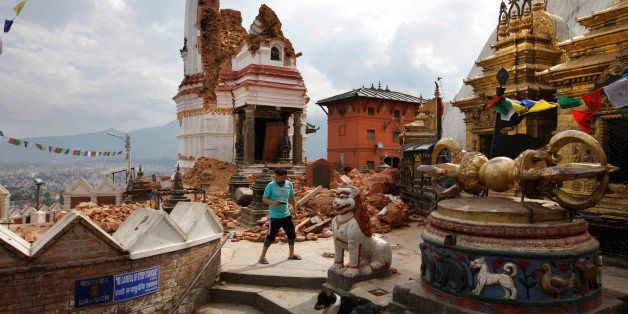 In this Thursday, April 30, 2015 photo, a man walks through the famous Swayambhunath stupa after it was damaged in the April
