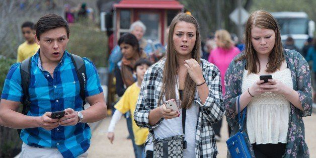 Three  teens walk with their smartphones as they walk outside the Natural History Museum  in Washington on April 8, 2015. A P