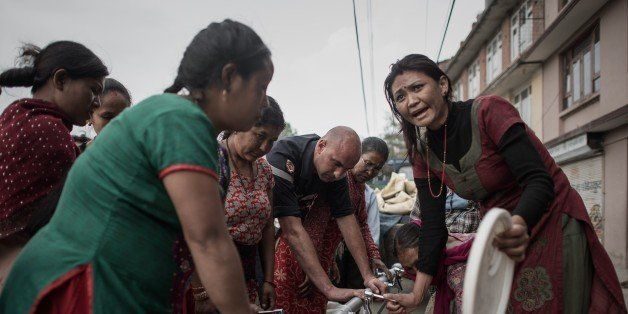 Women get water distributed as relief aid outside Bungamati village in the outskirts of Kathmandu on May 8, 2015. The 7.8 mag