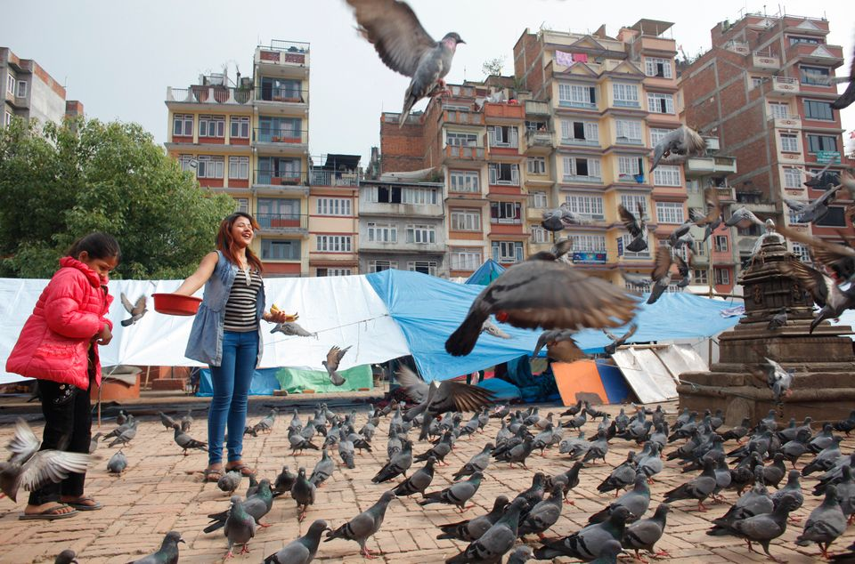 Nepalese girls feed pigeons after visiting a temple in Kathmandu, Nepal, Saturday, May 2, 2015. A week after the devastating