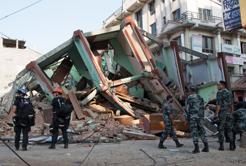 Rescue workers stand beside a building that collapsed in an earthquake in Kathmandu, Nepal, May 12, 2015.