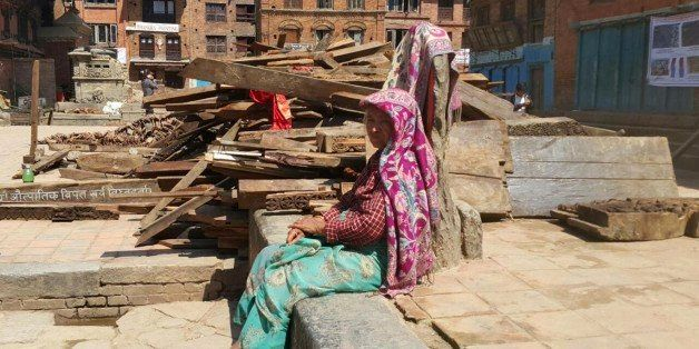A Nepalese woman sits outdoors after another earthquake in Bhaktapur, Nepal, Tuesday, May 12, 2015. A major earthquake has hi