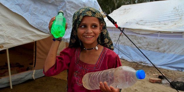 A girl displaced by floods smiles as she carries bottles of drinking water at a camp near Mirpur Khas, in Pakistan's Sindh pr