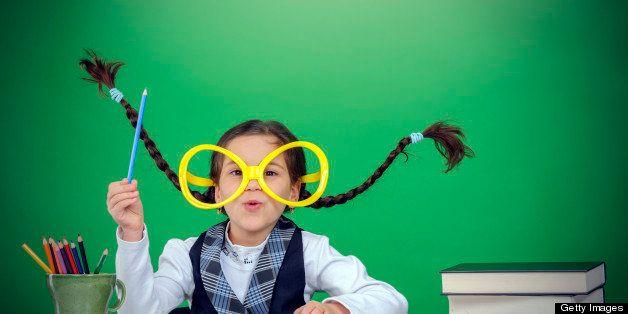 little smart girl wearing eyeglasses and blue pen.