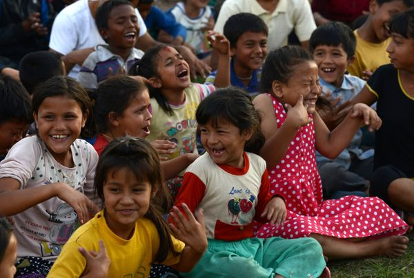 Nepalese children participate in a 'laughter yoga' session to help relieve trauma among survivors of two earthquakes which st