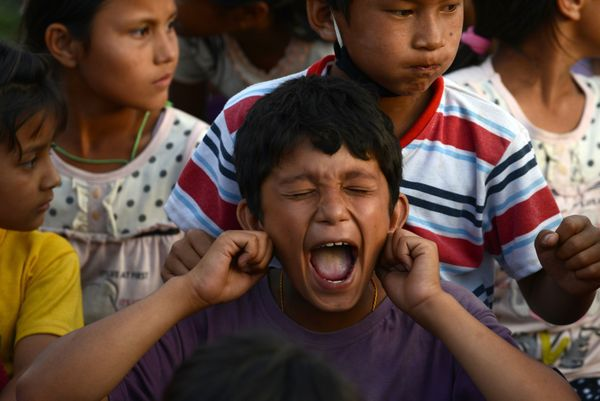 A Nepalese boy participates in a 'laughter yoga' session to help relieve trauma among survivors of two earthquakes which stru