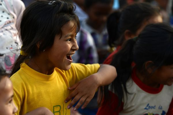 A Nepalese girl participates in a 'laughter yoga' session to help relieve trauma among survivors of two earthquakes which str