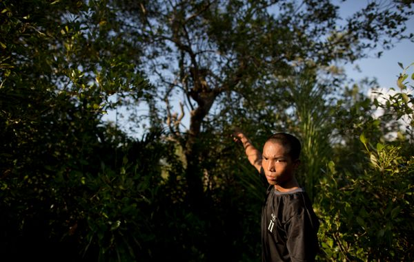 In this photo, taken on 3 November 2013, Min Thu, 17, a run-away boy soldier of Myanmar army, points at a tree that he used t