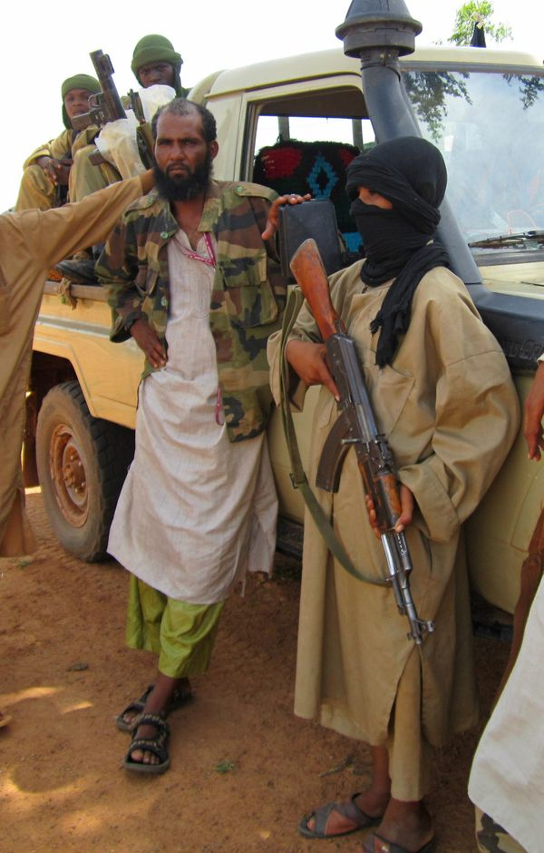 In this photo, taken on 27 September 2012, 13-year-old fighter Abdullahi, right, holds an AK-47 as his Islamist commanders lo