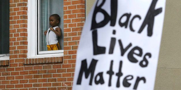 A child watches a protest march for Freddie Gray as it passes by, Wednesday, April 22, 2015, in Baltimore. Gray died from spi