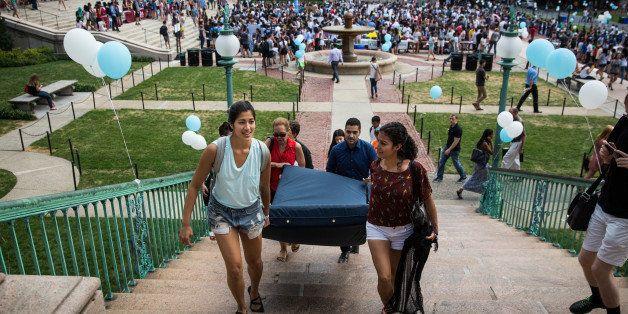 NEW YORK, NY - SEPTEMBER 05:  Emma Sulkowicz (L), a senior visual arts student at Columbia University, carries a mattress, wi