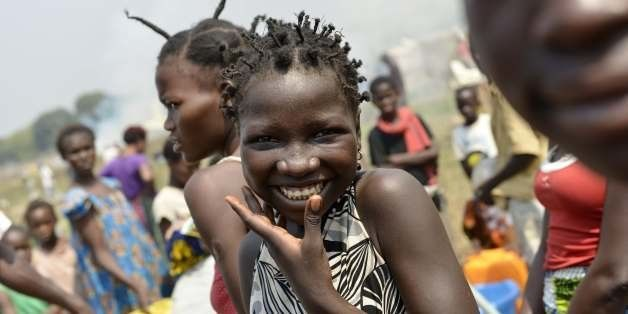 A woman smiles as internally-displaced people (IDPs) wait for water at the IDP camp near the international airport in Bangui