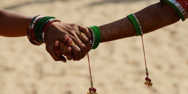 Girls dressed in traditional Rajasthani clothing hold hands as they wait for the start of a traditional dance presentation at