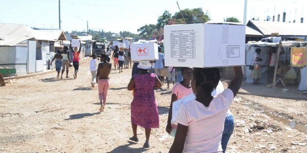 People  walk away after receiving medical kits to aid in the prevention of cholera on February 11, 2011 from the Internationa